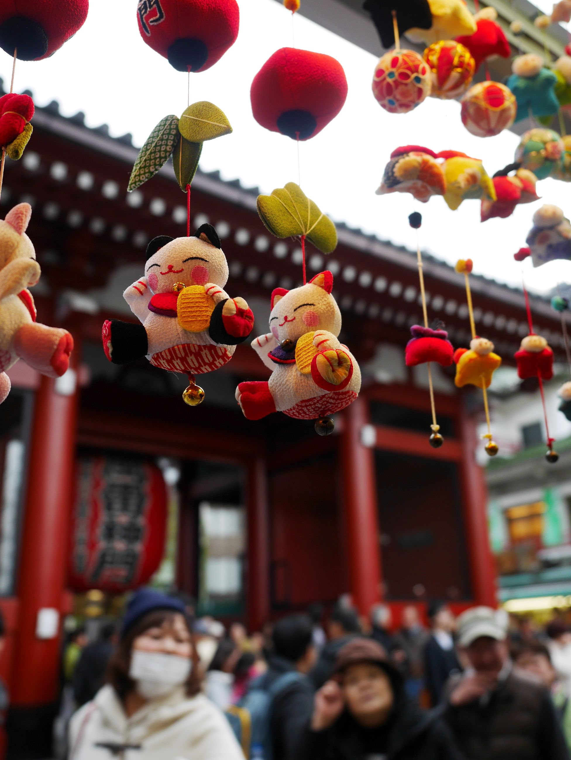 decoration, celebration, cultures, architecture, focus on foreground, tradition, built structure, person, large group of people, incidental people, lifestyles, illuminated, hanging, building exterior, leisure activity, men, lantern, city, multi colored