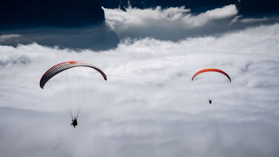 People paragliding in cloudy sky