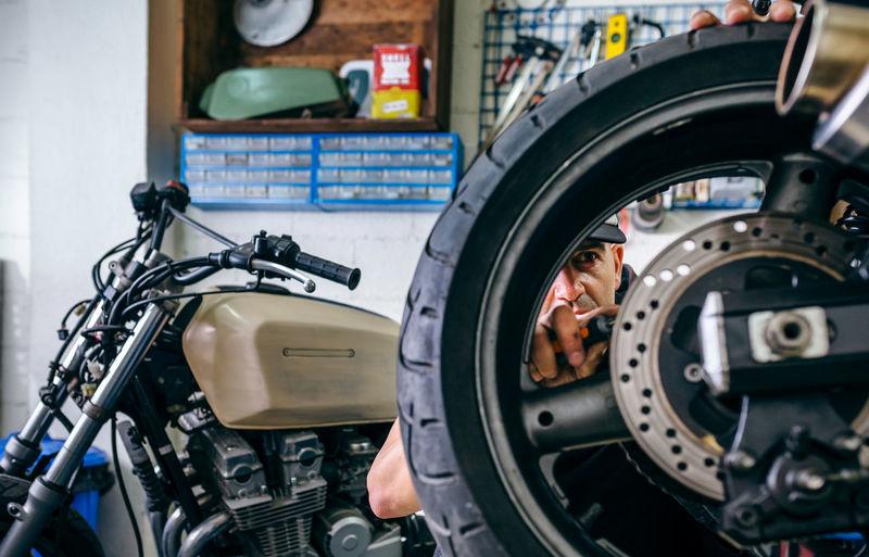 Man repairing motorcycle in garage