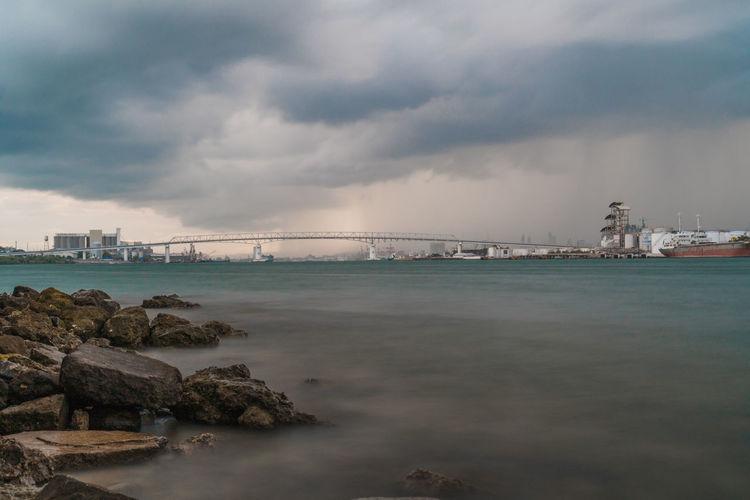 Bridge over sea against sky in city