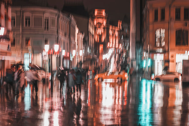 City street in rainy evening, abstract background of blurred people figures under umbrellas, orange tones. Intentional motion blur. Concept of seasons, weather, modern city Illuminated City Night Motion City Rainy Rain Blurred Motion Blur Abstract Evening Street Bright People Reflection Lamps Pavement Umbrella Water Group Of People Architecture Transportation Walking City Life Rainy Season