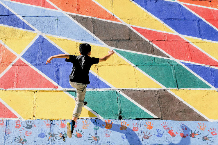 Rear view of boy jumping on colorful wall
