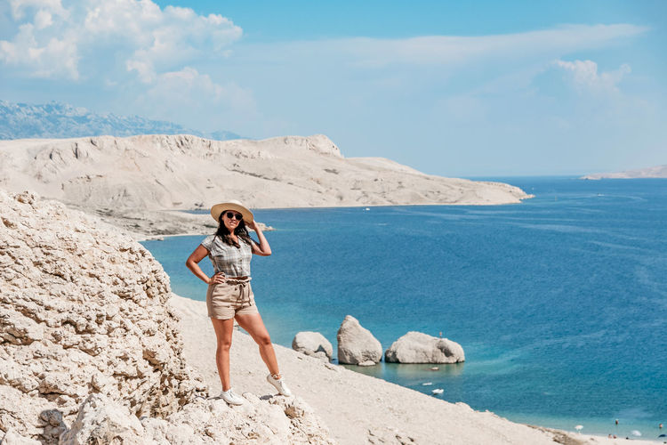 Front view of woman in summer clothes and sun hat standing on cliff overlooking spectacular beach.