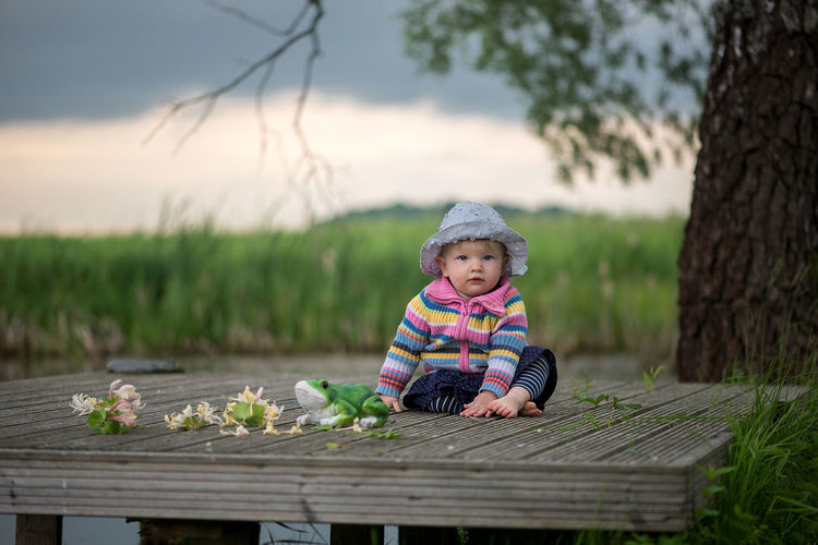 Portrait of cute baby girl sitting on pier against cloudy sky