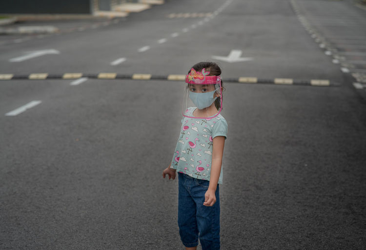 Child wearing face shield outdoor during coronavirus epidemic. new normal lifestyle, public places.