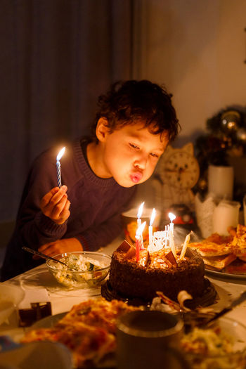 Cute curly boy with candles on birthday cake where is the candle in his hand