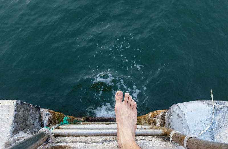 High Angle View Of Human Foot Next To Water