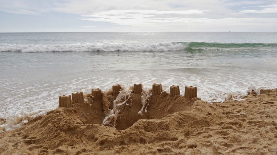 Sand castle catched by waves