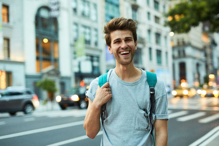 Portrait of young man standing on city street