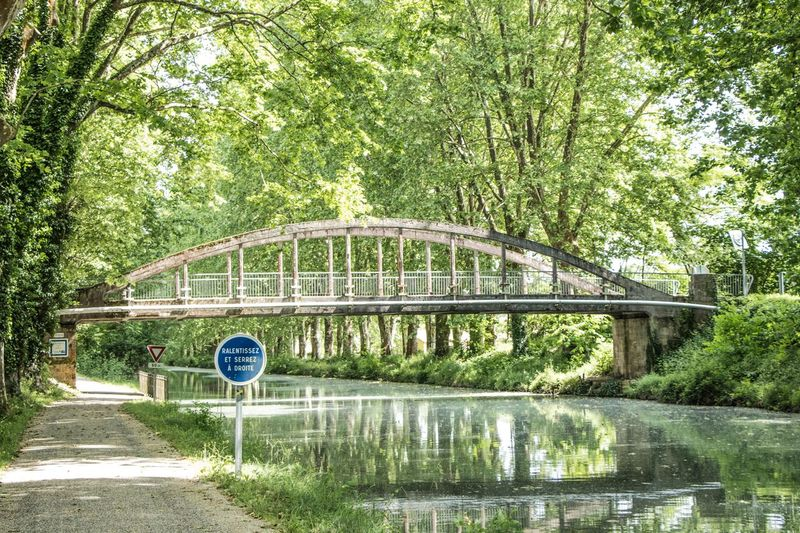 Fourques-sur-Garonne, commune in the Lot-et-Garonne department in south-western France. The Great Outdoors - 2018 EyeEm Awards Arch Arch Bridge Architecture Bridge Bridge - Man Made Structure Built Structure Connection Day Footbridge Green Color Nature No People Outdoors Park Plant Reflection Road Sign Transportation Tree Water