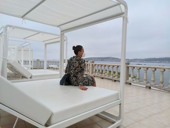 Full length of woman sitting on railing against sea