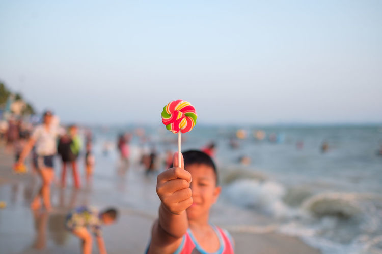 Beach Candy Day Focus On Foreground Hand Holding Horizon Over Water Land Leisure Activity Lifestyles Nature One Person Outdoors Portrait Real People Sea Sky Standing Sweet Food Water