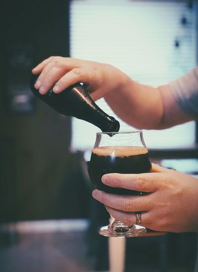 Close-up of hand pouring stout beer drink