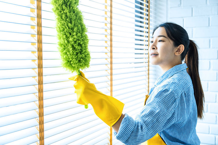 Side view of woman cleaning window at home