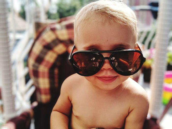 Portrait of shirtless baby girl wearing sunglasses