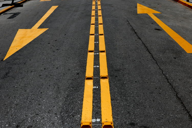 View Of Yellow Diving Lines And Arrows On Asphalt Road Arrow Symbol Asphalt City Communication Day Direction Dividing Line Guidance High Angle View Marking No People Outdoors Road Road Marking Rules Safety Sign Street Symbol The Way Forward Transportation Yellow