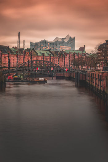 Bridge over river amidst buildings in city at sunset