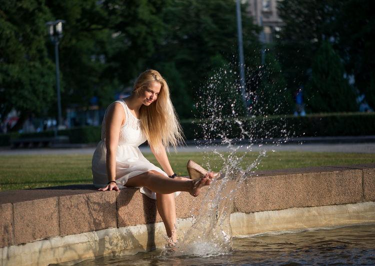 Woman Dangling Legs In Swimming Pool