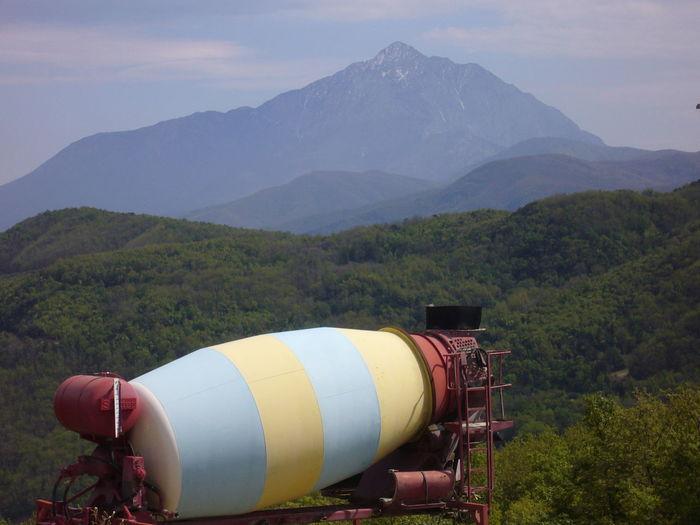 Scenic view of concrete mixer against landscape
