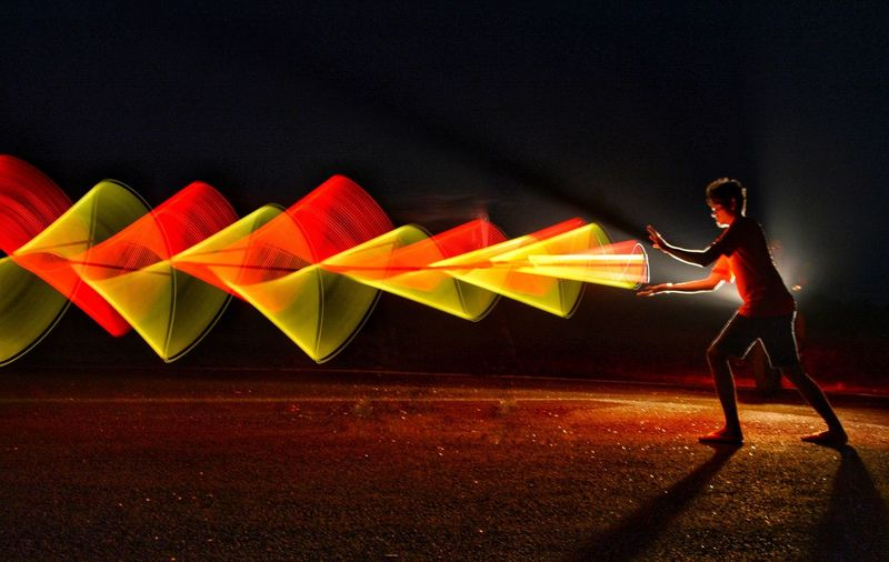 Side View Of Young Man With Illuminated Light Painting Standing Against Sky At Night