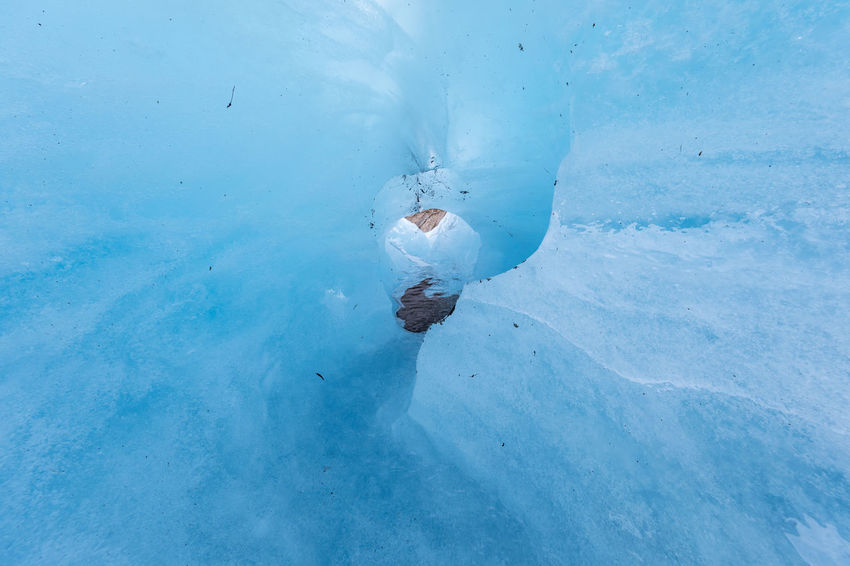 Inside an icy valley on a melting glacier looking through a hole towards a rock face Melting Arctic Beauty In Nature Blue Climate Change Cold Temperature Crevasse Day Environmental Issues Extreme Terrain Frozen Full Frame Glacier Hole Ice Iceberg - Ice Formation Outdoors Polar Climate River Rock - Object Summer The Way Forward Valley Water Winter
