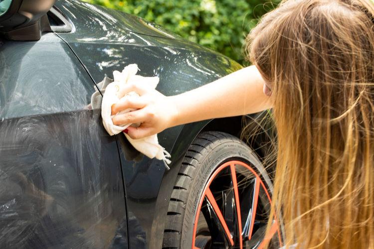 Close-up of teenage girl polishing car