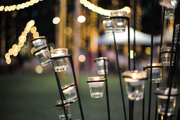 Close-up candle in small glass jars in the steel holder with blurred bokeh lights background