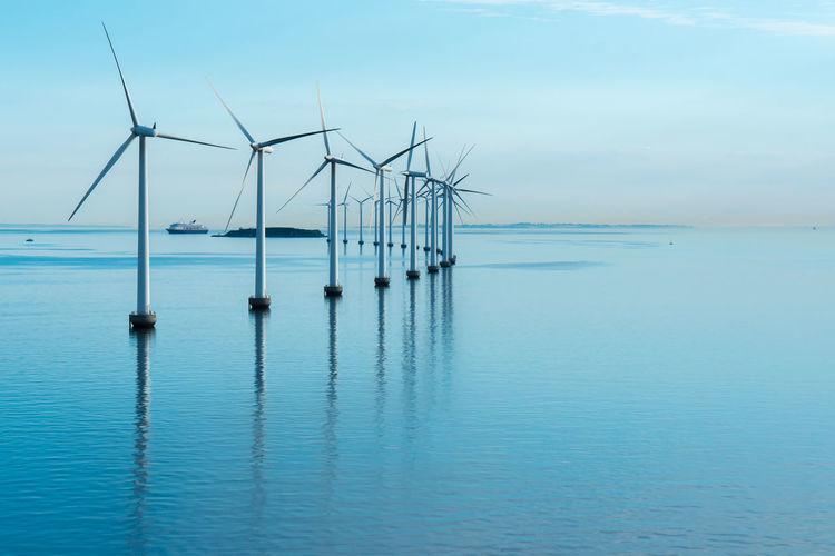 Windmills on sea against sky