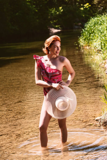 Full length of woman holding hat standing in water