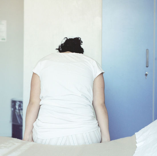Rear view of woman standing on bed