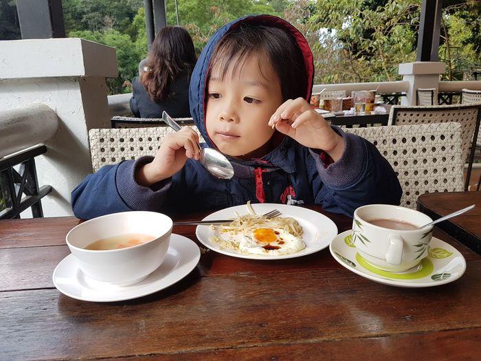 Boy having food at table in restaurant
