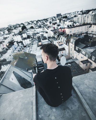 Young man photographing cityscape against sky