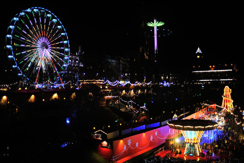 Illuminated ferris wheel and buildings in city at night