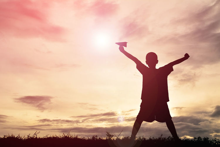 Silhouette boy with paper airplane standing with arms outstretched during sunset