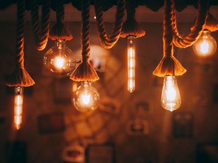 Illuminated light bulbs hanging indoors