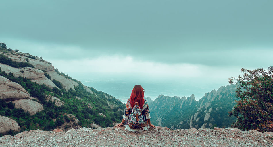 Rear View Of Female Hiker Sitting On Mountain Against Sky