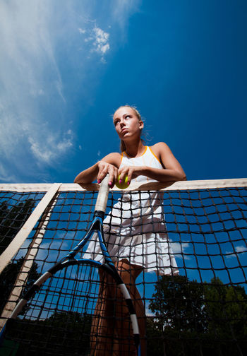 Beautiful young woman in a white suit and tennis racket in her hands standing behind the net. Bottom view One Person Low Angle View Sky Young Adult Front View Full Length Lifestyles Real People Day Young Women Nature Blue Portrait Women Clothing Leisure Activity Cloud - Sky Fashion Outdoors Beautiful Woman