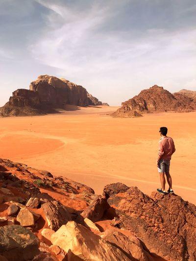 Young man on rocky formation in wadi rum desert in jordan