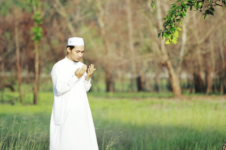 Young Man Praying On Grassy Field