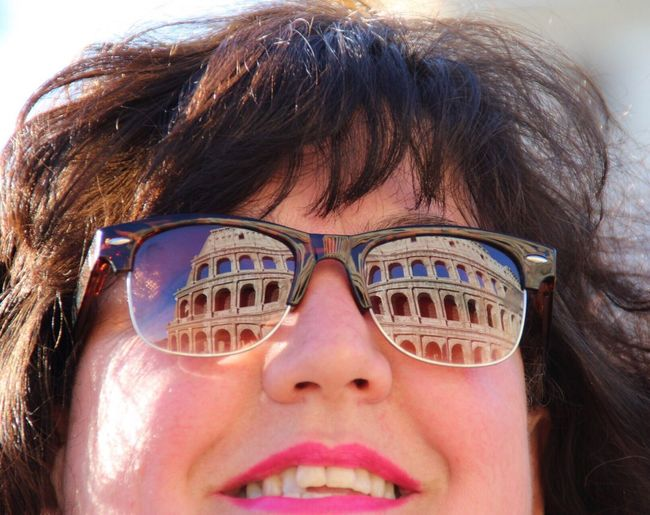 Smiling woman wearing sunglasses with reflection of colosseum