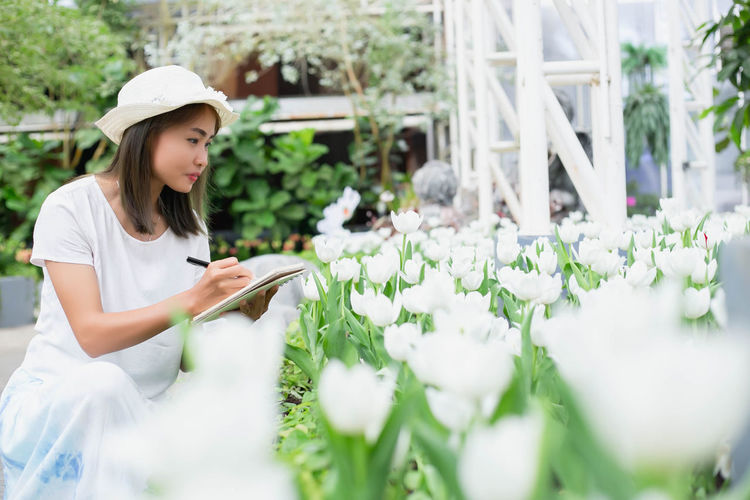 Side view of young woman holding red flowering plants
