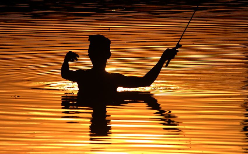 Silhouette man by lake against sky during sunset