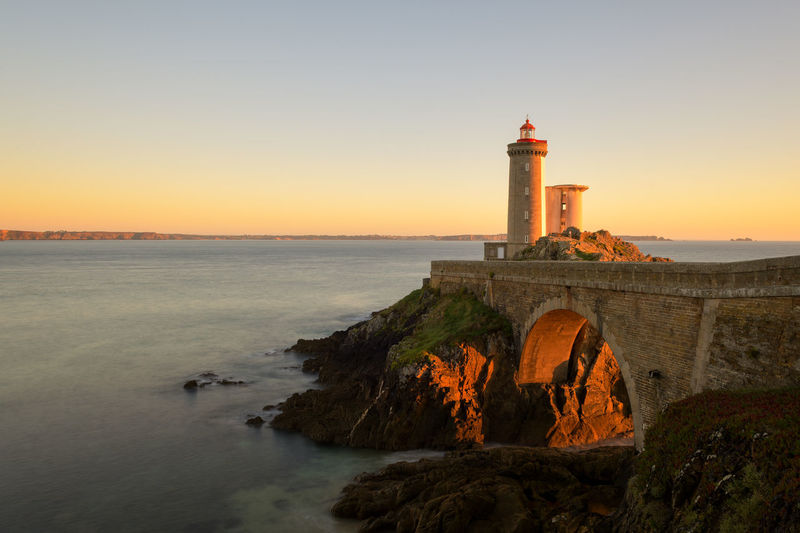 Lighthouse by sea against clear sky during sunset