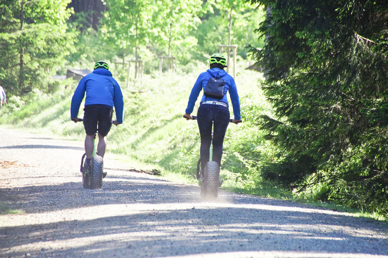 Rear View Of People Cycling Walking On Dirt Road