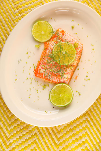 Salmon serving with fresh dill Home Cooking Homemade Food Natural Light Citrus Fruit Close-up Entree Fish Food Fresh Dill Fresh Fruit Freshness Healthy Eating Indoors  Lime No People Overhead Ready-to-eat Salmon Seafood Serving Size Studio Shot Vertical White Platter