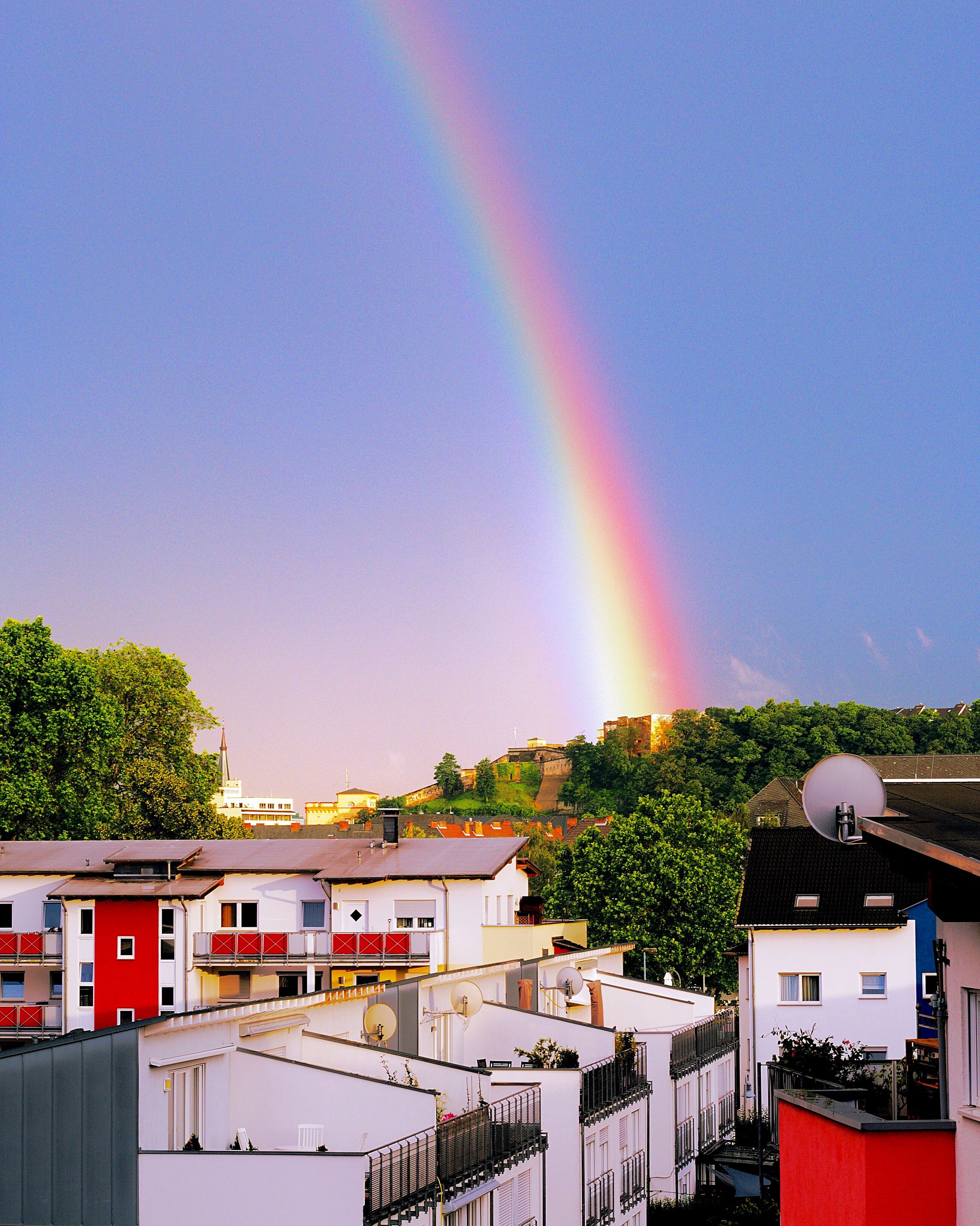 rainbow, architecture, built structure, tree, multi colored, sky, scenics, beauty in nature, nature, outdoors, no people, landscape, mountain, idyllic, blue, town, tranquil scene, tranquility, day, travel destinations, residential district, green color, cloud - sky, growth