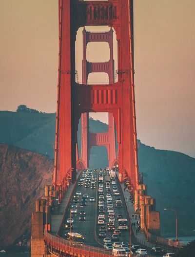 High angle view of vehicles on golden gate bridge against sky in city during sunset