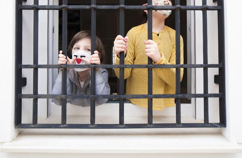 Siblings wearing masks looking through window