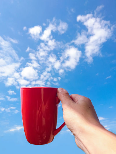 Midsection of person holding drink against blue sky