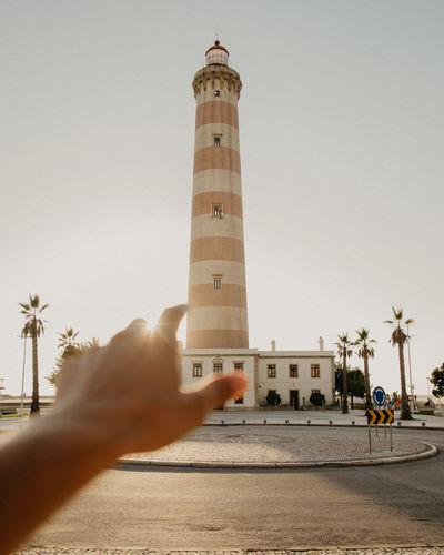 Hand gesturing towards lighthouse against clear sky